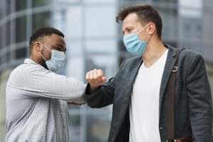two-colleagues-touching-elbows-outdoors-during-pandemic